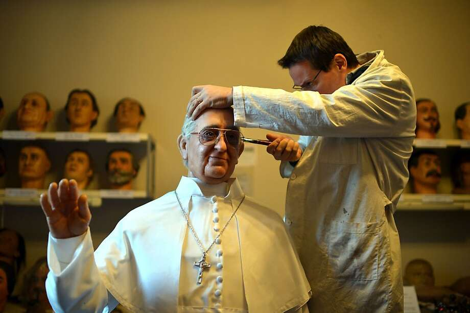 Your ear is filled with wax, Your Grace: Fernando Canini, director of Rome's wax museum, attends to the new statue of Pope Francis in the Eternal City. Photo: Gabriel Bouys, AFP/Getty Images
