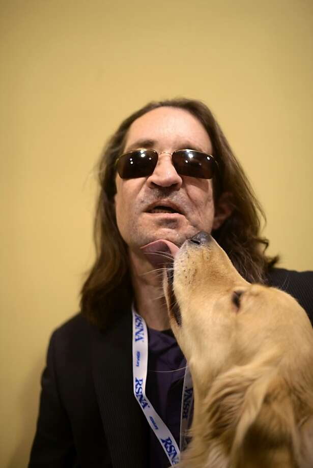 A new face and new hope: Dallas Wiens, the nation's first full-face transplant patient, receives a kiss from his guide dog, Charlie, at McCormick Place in Chicago. Despite still visible facial scars from the March 2011 surgery, Wiens looks and sounds like a recovered man. Medical imaging shows new blood vessel networks have formed, connecting transplanted skin with the patients' facial tissue. Photo: Paul Beaty, Associated Press
