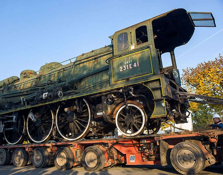 """Vintage loco piggybacks on truck:A """"Pacific"""" locomotive catches a ride on a flatbed truck from its exhibition area in Saint-Pierre-des-Corps, France, to a former Royal Air Force warehouse in the same town, where it will be restored. Built in 1938 in Calais, the train carried passengers traveling between Paris and London. Photo: Guillaume Souvant, AFP/Getty Images"""