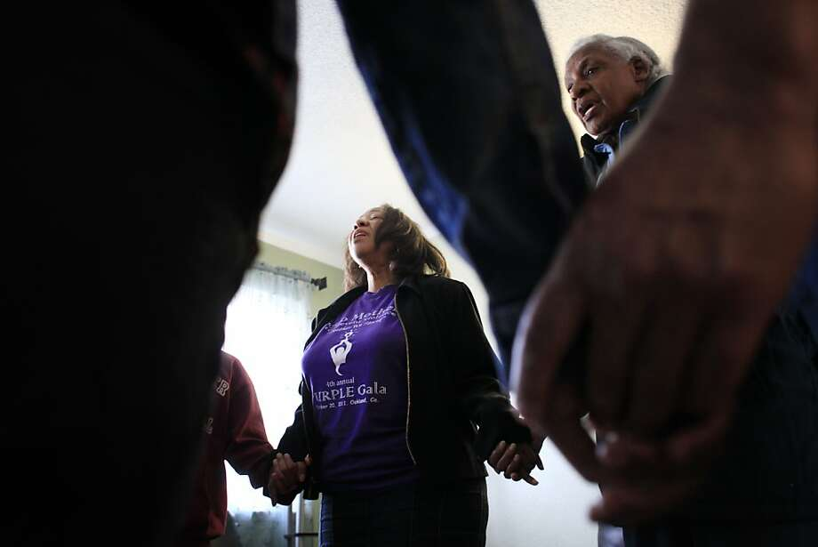 Lorrain Taylor (center), with sister Mary Amara by her side, prays after a meeting with Yokia Mason and her family to discuss their fear of violence after gunfire near their East Oakland home injured seven people. Photo: Mike Kepka, The Chronicle