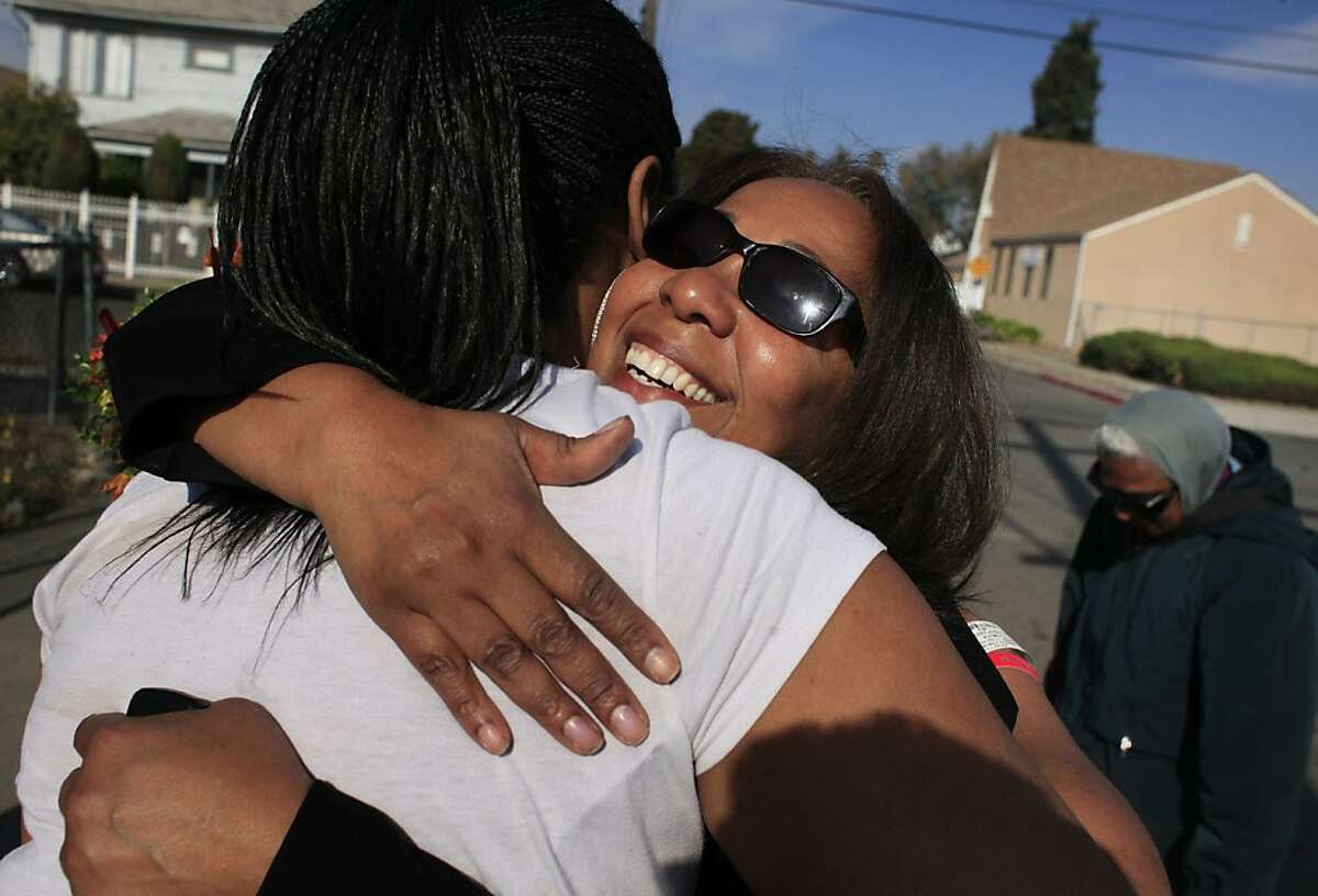 Lorrain Taylor (right) hugs longtime client Yokia Mason, who lost a brother and a cousin to gun violence. Mason says Taylor has taught her to create peace within her own house.