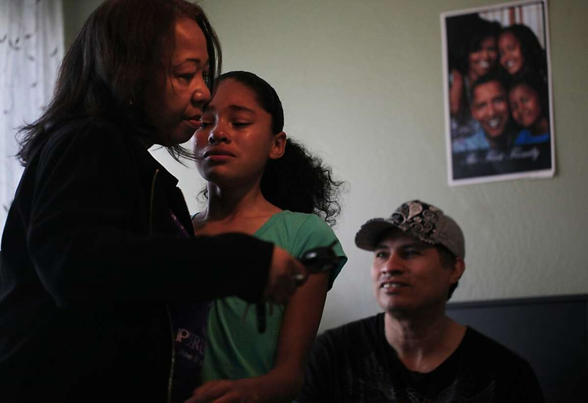 Taylor comforts 11-year-old Karina Magana with her father, Vincente Magana, nearby in their East Oakland home.