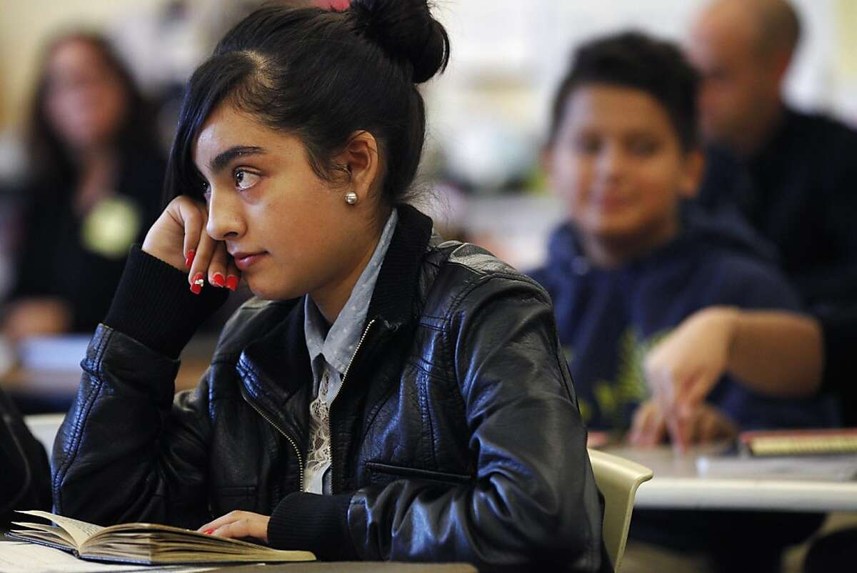 Gisselle Mendoza, 14, listens to Eva Kellogg during the 8th grade English class November 21, 2013 at Aspire Lionel Wilson College Preparatory Academy in Oakland, Calif. Based upon the previous year's teacher evaluation process, Aspire charter schools have started giving out bonuses to well preforming teachers. Kellogg was one of the teachers who was chosen to receive a bonus.