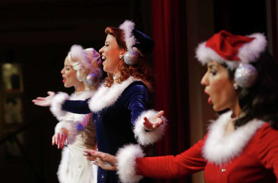 "In this Monday, Nov. 18, 2013 photo, Courtney Boe, left, Mandi Ridgell, center, and Christina Perez, members of the singing group ""The Victory Belles,"" modeled after the WWII era group The Andrew Sisters, rehearse for their upcoming Christmas show, ""A Swingin' Christmas,"" at the Stage Door Canteen at the National WWII Museum in New Orleans. The sexy, classy, glamorous 20-somethings perform year-round at the National World War II Museum in New Orleans in the tradition of the wartime entertainers of Hollywood's golden age. (AP Photo/Gerald Herbert) ORG XMIT: LAGH202 Photo: Gerald Herbert / AP"