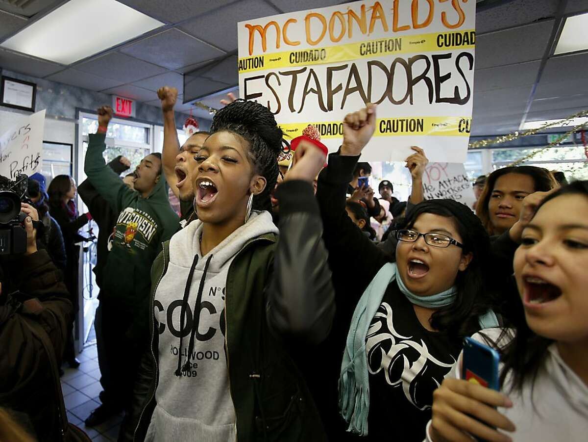 Protester including Rikia White (center) moved into the restaurant and urged the workers to join them Thursday December 5, 2013 in Oakland, Calif. On a day of national protest against the wages paid to fast food workers, dozens protested in front of a McDonalds on Jackson Street and entered the restaurant.