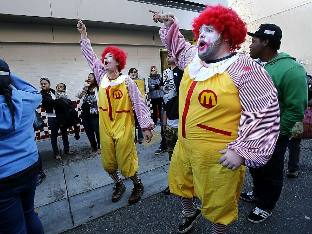 Two men dressed as Ronald McDonald danced with others on the drive in side of the restaurant Thursday December 5, 2013 in Oakland, Calif. On a day of national protest against the wages paid to fast food workers, dozens protested in front of a McDonalds on Jackson Street and entered the restaurant.