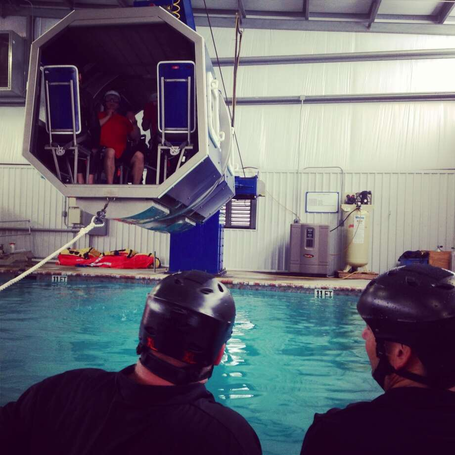Students at Falck Safety Services use a simulator to practice escaping from a helicopter crash, part of training for work in an offshore oil field. Photo: Peter Holley, Houstonia Magazine
