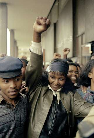 Black South African leader Winnie Mandela, wife of jailed leader Nelson Mandela, raises a clenched fist after appearing at a Johannesburg magistrate's court, Dec. 1986.  Mrs. Mandela was held by police in Soweto the previous day for defying an order banning her presence there. Photo: Greg English, Wire / AP1986