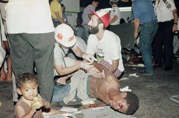 A young child sits next to a man receiving medical attention on Sunday, Feb. 11, 1990 in Cape Town, South Africa after he was wounded by police during violent clashes. Clashes broke out while supporters of the ANC gathered in Cape Town's Grand Parade to hear their leader Nelson Mandela speak. Photo: Ad
