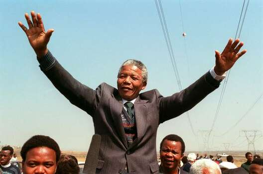 South African National Congress President Nelson Mandela addresses a crowd of residents from the Phola park squatter camp during his tour of townships in 1990. Photo: Getty Images