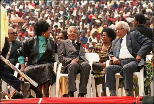 South African National Congress (ANC) President Nelson Mandela (c), together with his then-wife Winnie (l), Walter Sisulu (r), Veteran ANC secretary-general and Robben Island prisoner and Sisulu's wife Albertina (2nd-r), are seated 13 February 1990 on the platform in the middle of Soweto Soccer City stadium, during a rally attended by over 100,000 people, to celebrate Mandela's release from the jail 11 February 1990. Photo: Getty Images