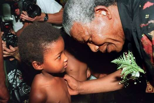 South African National Congress (ANC) leader Nelson Mandela listens 31 January 1994 to a little boy at a training farm where he is campaigning for April general elections. Photo: Getty Images