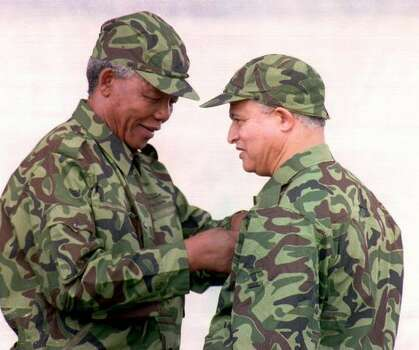 African National Congress (ANC) President Nelson Mandela (L) presents a medal for bravery to James April, member of the Umkhonto We Sizwe (armed wing of the ANC) during the 32nd anniversary celebrations of the ANC army in Soweto, South Africa, in December 1993. Photo: Getty Images