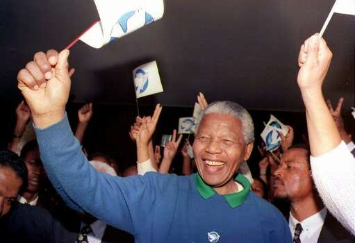 ANC president Nelson Mandela waves a flag bearing the peace symbol, while leading a demonstration to mark South Africa's national day of peace and prayer with calls for individuals to commit themselves to end the violence ravaging the country, outside ANC headquarters in Johannesburg 02 September 1993. Photo: Getty Images