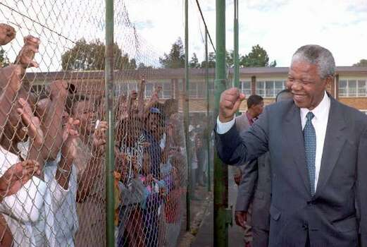 African National Congress (ANC) President Nelson Mandela greets supporters behind the fence in a mining town of Randfontein west of Johannesburg 25 November 1993. Mandela tours the area as part of his campaign for the 27 April 1994 election. Photo: Getty Images