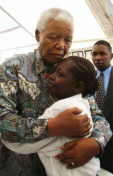 Former South African president Nelson Mandela hugs Babalwa Tembani (20), who was infected with the HIV virus after being raped by her uncle at the age of 14, at the Nolungile Clinic at Site C in Khayelitsha, Cape Town 12 December 2002. She is currently on ante-retroviral treatment and is involved in education work in schools and youth centers. Nelson Mandela visited the clinic which is run by Medecins Sans Frontiers and is the first site in South Africa where ante-retro viral treatment is offered for free in public community centres. Photo: Getty Images