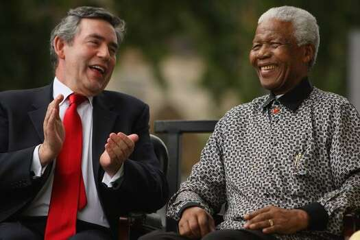 British Prime Minister Gordon Brown applauds ex-South African President Nelson Mandela during a statue unveiling ceremony in Nelson Mandela's honor at Parliament Square on August 29, 2007 in London, England. The statue depicting Nelson Mandela delivering a speech, by sculptor Ian Walters, is nine-feet (2.7-metres) high, made of bronze and faces the Houses of Parliament. Photo: Getty Images