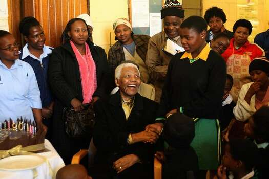Former South African president and Nobel Peace prize laureate Nelson Mandela(c) pays a surprise visit on August 04, 2008 to the Banakekele Hospice in Kew, Johannesburg. He donated the two birthday cakes he had received earlier in the day from the South African national rugby and football teams. Photo: Getty Images