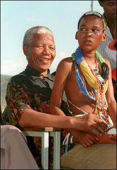 African National Congress (ANC) Nelson Mandela shown in a file photo dated 07 March 1994 posing with a young girl at a People's Forum at Sekororo in Lebowa in Northern Transvaal, the heartland of white Afrikanderdom. Photo: Getty Images