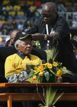 An aide places a cap the the head of former South African President Nelson Mandela, age 90, to protect him from the sun at a campaign rally April 19, 2009 in Johannesburg, South Africa. Mandela made a surprise appearance at the final major election rally for the ruling African National Congress ahead of national elections on Wednesday. The ANC is expected to win by a wide margin but faces its toughest competition from rival parties yet, since it came to power in 1994. Photo: Getty Images