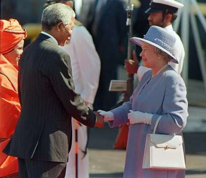 South African President Nelson Mandela greets Queen Elizabeth II of Britain upon her official arrival at Cape Town's Waterfront 20 March 1995. The Queen is on celebratory week-long state visit to South Africa. Photo: Getty Images