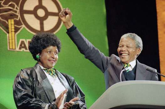South African anti-apartheid leader Nelson Mandela with his wife Winnie at his side, raises his fist as he acknowledges the cheers of thousands at a rock concert  Monday, April 16, 1990 at London's Wembley Stadium. Photo: Martin Cleaver, Wire / 1990 AP