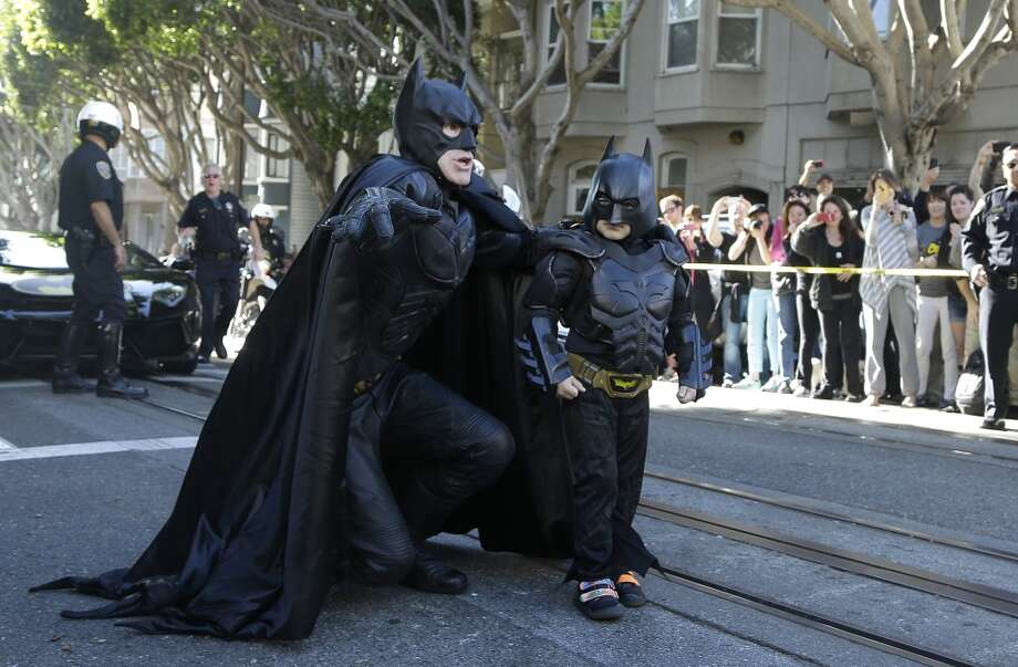 """Miles Scott, dressed as Batkid, right, walks with Batman before saving a damsel in distress in San Francisco, Friday, Nov. 15, 2013.  San Francisco turned into Gotham City on Friday, as city officials helped fulfill Scott's wish to be """"Batkid.""""Scott, a leukemia patient from Tulelake in far Northern California, was called into service on Friday morning by San Francisco Police Chief Greg Suhr to help fight crime, The Greater Bay Area Make-A-Wish Foundation says. (AP Photo/Jeff Chiu) Photo: Jeff Chiu, Associated Press"""