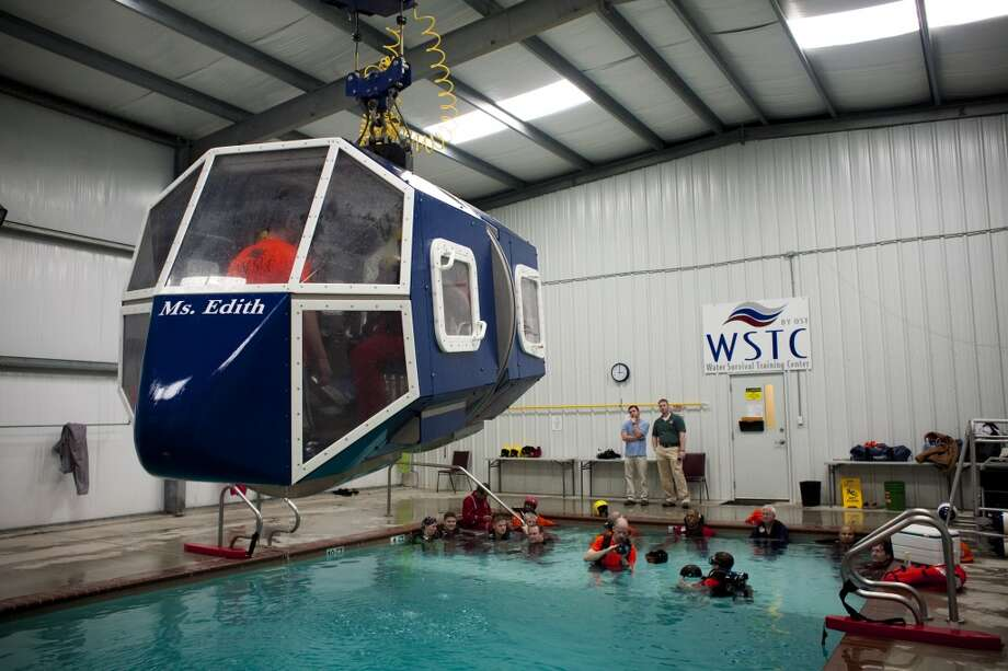Participants are instructed in Helicopter Underwater Egress Training (HUET) and other open water survival techniques  in preparation for upcoming trips to offshore oil and gas platforms in the Gulf of Mexico Feb. 15, 2010 in Brookshire, TX. All workers, contractors and visitors are now required to do the training, which simulates a helicopter crash (in a swimming pool) and emergency steps used to free oneself while underwater. Photo: Eric Kayne, For The Chronicle