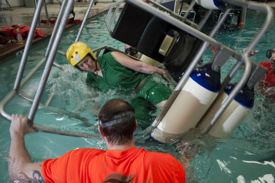 Charlie Brittan is taught how to escape from a sinking helicopter inside a shallow water egress training chair during a class in open water survival techniques, taught by Garrett Hindt, center Feb. 15, 2010 in Brookshire, TX. All workers, contractors and visitors are now required to do the training, which also incorporates a simulated helicopter crash (in a swimming pool) and emergency steps used to free oneself while underwater. Photo: Eric Kayne, For The Chronicle