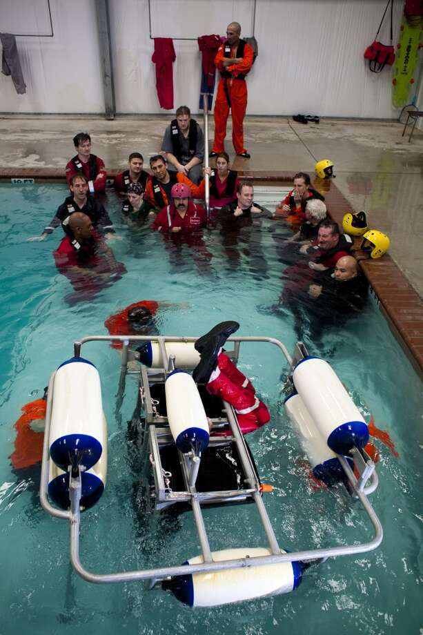 Participants are taught how to escape from a sinking helicopter inside a shallow water egress training chair during a class in open water survival techniques, taught by Garrett Hindt, center Feb. 15, 2010 in Brookshire, TX. All workers, contractors and visitors are now required to do the training, which also incorporates a simulated helicopter crash (in a swimming pool) and emergency steps used to free oneself while underwater. Photo: Eric Kayne, For The Chronicle