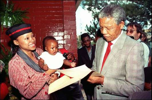 South African National Congress (ANC) President Nelson Mandela (r) signs 21 February 1990 an autograph at his Soweto home as his daughter Zinzi and grandchild Bambata are looking on. Photo: Getty Images