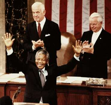 This file photo taken 26 June 1990 shows Nelson Mandela, the former deputy president of the African National Congress as he raises his arms to acknowledge applause from members of the Senate and House of Representatives in Washington,DC. Mandela was the third private citizen in history to address a joint meeting of the US Congress. Standing above Mandela are former House Speaker Thomas Foley (L) and Senate Majority Leader Robert Byrd (R). Photo: Getty Images