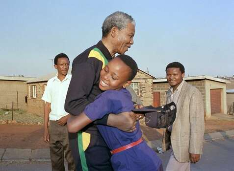 South African National Congress President Nelson Mandela hugs, October 1990, a young Sowetan girl as he visits the black township near Johannesburg. Photo: Getty Images