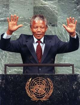 South African National Congress (ANC) President Nelson Mandela smiles 22 June 1990 in New York, raising his arms over his head as he receives applause at the United Nations. Mandela urged the U.N. to maintain sanctions against South Africa until apartheid is abolished. Photo: Getty Images