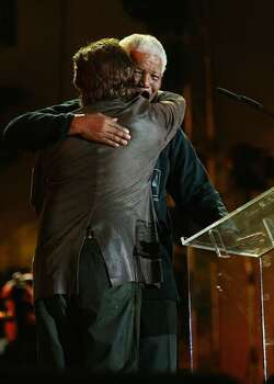 "Nelson Mandela hugs singer Bono at the ""46664 - Give One Minute of Your Life to AIDS"" concert at Greenpoint Stadium on November 29, 2003 in Cape Town, South Africa. The concert will benefit the Nelson Mandela Foundation and the fight against AIDS in Africa. Photo: Getty Images"