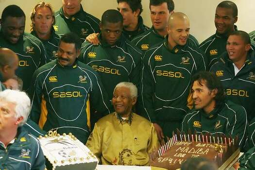 Former South African president and Nobel peace prize laureate Nelson Mandela (C) receives his 90th birthday greetings from the South African rugby and football national team on August 04, 2008 at the Nelson Mandela foundation in Johannesburg. Photo: Getty Images