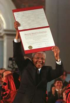 CAMBRIDGE, UNITED STATES: South African President Nelson Mandela shows his degree certificate to a large crowd at Harvard University in Boston, MA, after receiving the Honorary degree 18 September. Mandela is on an official visit in North America and will go to the United Nations, New York, Washington and Canada. Photo: Getty Images