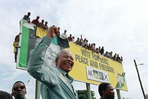 ANC youths wait for ANC President Nelson Mandela atop a billboard in a township outside Durban16 April 1994 prior to an election rally. Photo: Getty Images