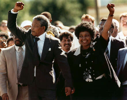 Nelson Mandela and wife Winnie, walking hand in hand, raise clenched fists upon his release from Victor prison, Cape Town, Sunday, February 11, 1990.  The African National Congress leader had served over 27 years in detention. Photo: GREG ENGLISH, Wire / 1990 AP