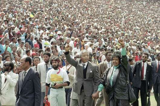 Nelson Mandela and Winnie Mandela give back power salutes as they enter Soweto's Soccer City stadium, South Africa Tuesday, Feb. 13, 1990. 120,000 thousand people packed the venue to hear his speech. Photo: Udo Weitz, Wire / AP1990