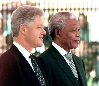 "President Clinton stands with South African President Nelson Mandela during the official arrival ceremony in Cape Town, South Africa, Thursday, March 26, 1998. Proudly becoming the first U.S. head of state to visit this onetime pariah nation, President Clinton Thursday  called for a partnership ""of mutual respect and mutual reward'' with the  new South Africa. Photo: J. SCOTT APPLEWHITE, Wire / AP1998"