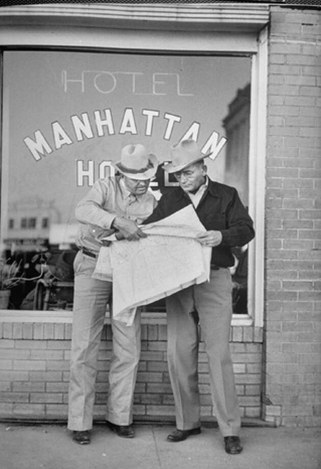Oil seekers T. J. Sterling (left) and A. B. Blaze consulting county map outside town's busiest trading spot.  (Photo by Joseph Scherschel//Time Life Pictures/Getty Images) Photo: Joseph Scherschel, Time & Life Pictures/Getty Image / Time Life Pictures