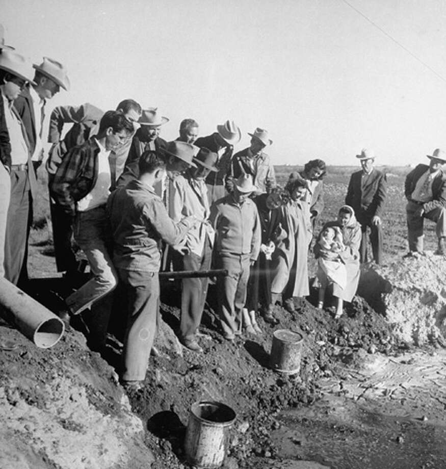 Crowd of neighbors standing in pasture of farmer Joe York (C, front row), watching for first sputter of oil to come from York's well.  (Photo by Frank Scherschel//Time Life Pictures/Getty Images) Photo: Frank Scherschel, Time & Life Pictures/Getty Image / Time Life Pictures