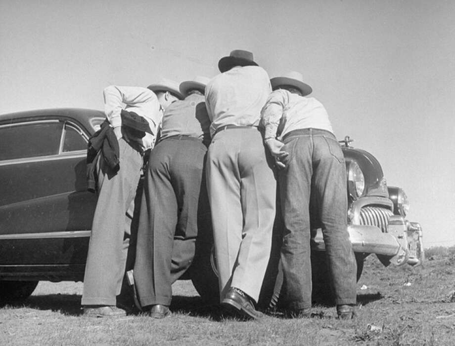 Oil scouts and lease men huddling over oil map on car hood before going on exploring tour.  (Photo by Joseph Scherschel//Time Life Pictures/Getty Images) Photo: Joseph Scherschel, Time & Life Pictures/Getty Image / Time Life Pictures