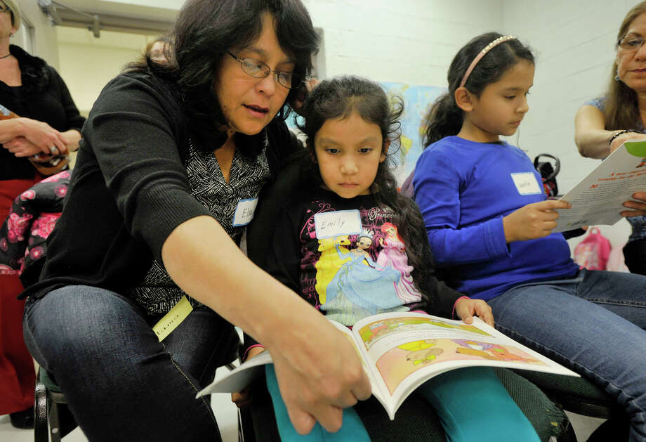 Elsa Martinez reads along with her five-year-old daughter, Emily Soraluz, during the adult-oriented English as second language family literacy class' family day at Stark Elementary School in Stamford, Conn., on Thursday, Dec. 5, 2013. The class consists of people that speak six languages from 12 countries. Elsa immigrated from Peru. Photo: Jason Rearick / Stamford Advocate