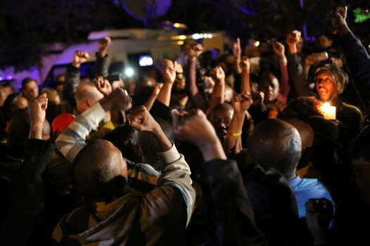 South Africans react as they pay tribute to former South African president Nelson Mandela following his death in Johannesburg on December 5, 2013. Mandela, the revered icon of the anti-apartheid struggle in South Africa and one of the towering political figures of the 20th century, has died aged 95. Mandela, who was elected South Africa's first black president after spending nearly three decades in prison, had been receiving treatment for a lung infection at his Johannesburg home since September, after three months in hospital in a critical state. Photo: ALEXANDER JOE, Getty Images / 2013 AFP