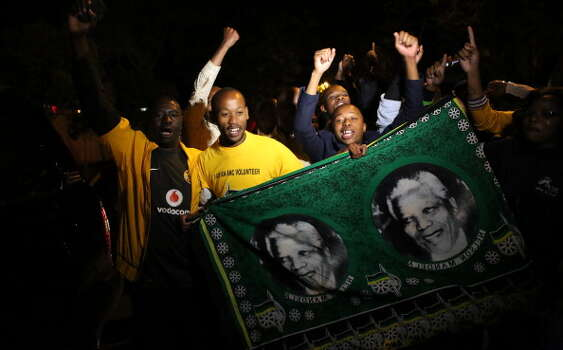 South Africans hold pictures of former South African president Nelson Mandela as they pay tribute following his death in Johannesburg on December 5, 2013. Mandela, the revered icon of the anti-apartheid struggle in South Africa and one of the towering political figures of the 20th century, has died aged 95. Mandela, who was elected South Africa's first black president after spending nearly three decades in prison, had been receiving treatment for a lung infection at his Johannesburg home since September, after three months in hospital in a critical state. Photo: ALEXANDER JOE, Getty Images / 2013 AFP