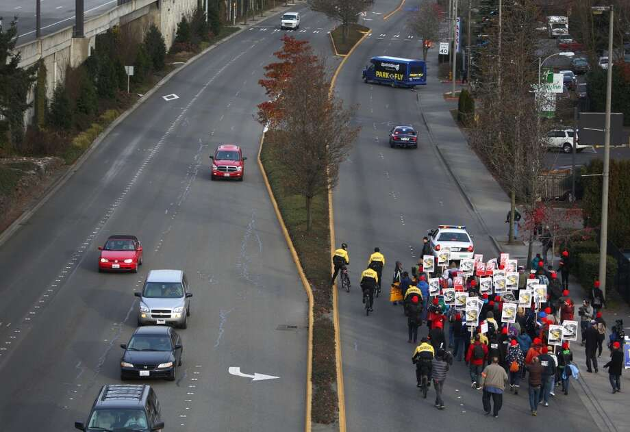 Fast food workers, labor organizers and other workers march on International Boulevard in SeaTac. The marchers are asking for a minimum wage of $15 per hour. The march, heading for Seattle, started in SeaTac, the city where a voter initiative to pay workers a minimum of $15 per hour just passed. Photographed on Thursday, December 5, 2013.  (Joshua Trujillo, seattlepi.com) Photo: JOSHUA TRUJILLO, SEATTLEPI.COM