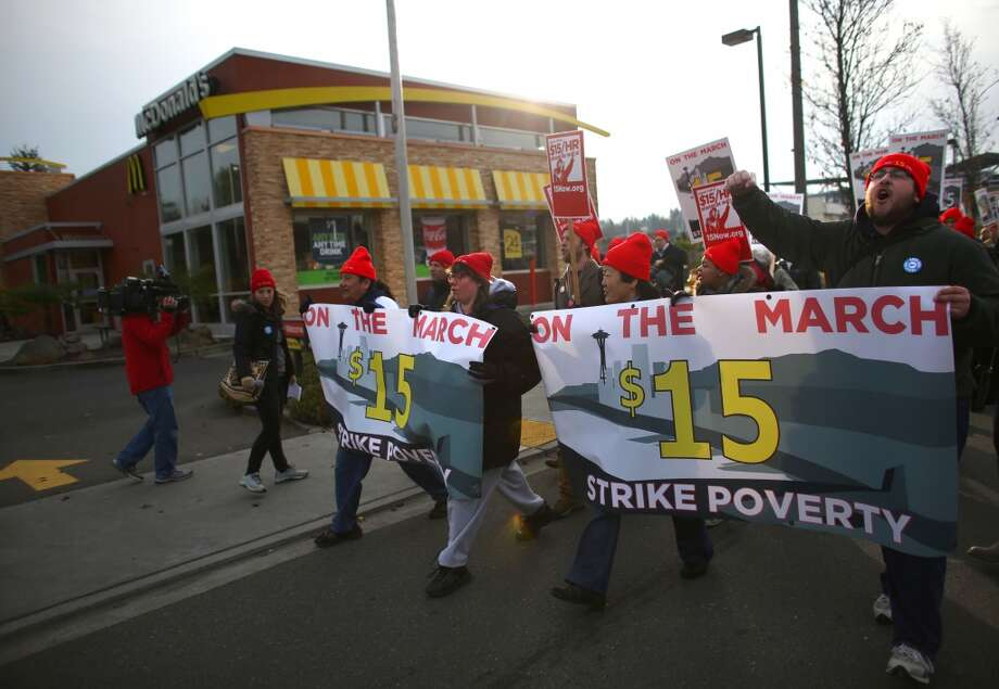 Fast food workers, labor organizers and other workers march past fast food restaurants on Pacific Highway South in Tukwila, Wash. The marchers are asking for a minimum wage of $15 per hour. The march, heading for Seattle, started in SeaTac, the city where a voter initiative to pay workers a minimum of $15 per hour just passed. Photographed on Thursday, December 5, 2013.  (Joshua Trujillo, seattlepi.com) Photo: JOSHUA TRUJILLO, SEATTLEPI.COM