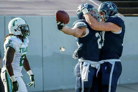 Rice running back Turner Petersen (26) celebrates after scoring on a 19-yard touchdown pass as Tulane safety Darion Monroe (2) walks away during the first quarter of a college football game at Rice Stadium, Saturday, Nov. 30, 2013, in Houston.